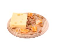 Cheese on board with nuts and orange. Royalty Free Stock Photo