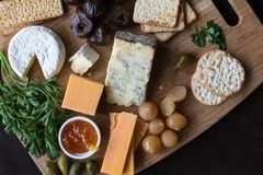 Cheese board serving with figs, caper berries, jam, parsley and pickled onions. Top view photograph with copy space - stock photos