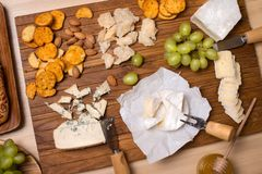 Cheese board. Various types of cheese. Cheese plate with cheeses Parmesan, Brie, Camembert and Roquefort serving on wooden board.  royalty free stock photography