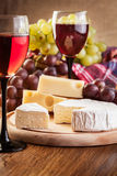 Cheese with a bottle and glasses of red wine Stock Images