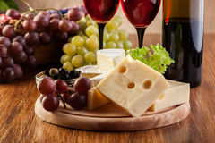 Cheese with a bottle and glasses of red wine Stock Photos