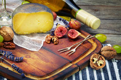 Cheese, a bottle of  wine with grape, walnut  and fig on old woo Stock Photo