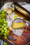Cheese, a bottle of  wine with grape, walnut  and fig on old woo Royalty Free Stock Images