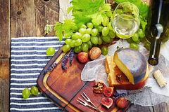 Cheese, a bottle of wine with grape, walnut and fig on old woode Royalty Free Stock Image