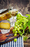 Cheese, a bottle of wine with grape, walnut and fig on old woode Stock Photo