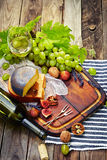 Cheese, a bottle of wine with grape, walnut and fig on old woode Royalty Free Stock Photos