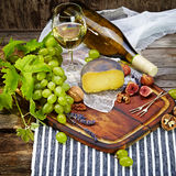 Cheese, a bottle of wine with grape, walnut and fig on old woode Stock Image