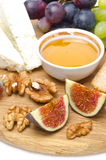 Cheese, bread, figs, grapes, honey and nuts on wooden board Royalty Free Stock Photography