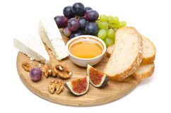 Cheese, bread, figs, grapes, honey and nuts on a wooden board Royalty Free Stock Photography