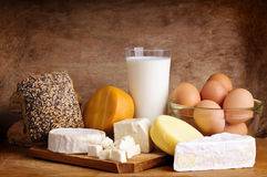 Cheese, bread, milk and eggs. Still life with dairy products, milk, eggs, bread and cheese on a vintage wooden background Stock Images