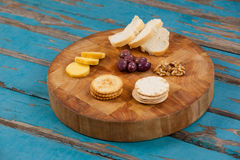 Cheese, bread, olives, biscuits and walnut on wooden board Royalty Free Stock Images