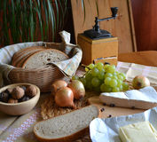Cheese, bread, onions, wine and grinder Stock Photos