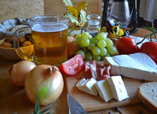 Cheese, bread, onions, wine, tomatoes and beer Royalty Free Stock Photos