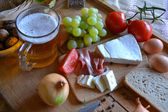 Cheese, bread, onions, wine, tomatoes and beer Stock Image