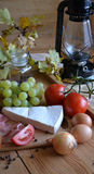 Cheese, bread, onions, wine, tomatoes and a kerosene lamp Stock Images