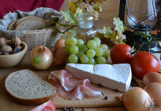 Cheese, bread, onions, wine, tomatoes and a kerosene lamp Royalty Free Stock Images