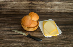 Cheese, bread rolls and knife Stock Photography