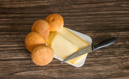 Cheese, bread rolls and knife. On a wooden background Stock Photos