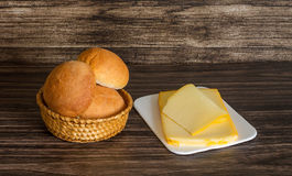 Cheese and bread rolls. On a wooden background Stock Photos