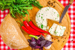 Cheese and bread on the wooden board. With chili, garlic and ruccola Royalty Free Stock Photos