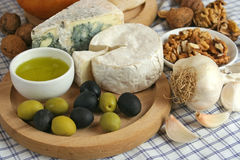 Cheese breakfast. Mediterranean breakfast setup with olives, cheese, olive oil, garlic and wine Stock Photo