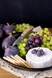 Cheese Brie Camembert with Figs and Grapes on wooden table Food for Wine Figs Green and Red Grapes Crackers Knife Plate Snacks Ver. Tical royalty free stock photography