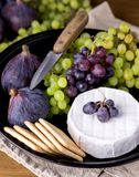 Cheese Brie Camembert with Figs and Grapes on wooden table Food for Wine Figs Green and Red Grapes Crackers Knife Plate Snacks Ver. Tical Above stock images
