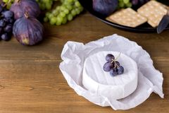 Cheese Brie Camembert with Figs and Grapes on wooden table Food for Wine Figs Green and Red Grapes Crackers Knife Plate Snacks Cop. Y Space stock image