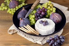 Cheese Brie Camembert with Figs and Grapes on wooden table Food for Wine Figs Green and Red Grapes Crackers Knife Plate Snacks. Cheese Brie Camembert with figs stock photo