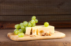 Cheese with brush of grapes Royalty Free Stock Image