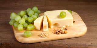 Cheese with brush of grapes and walnuts Royalty Free Stock Photo