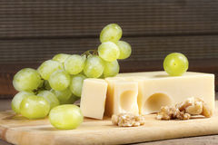 Cheese with brush of grapes and walnuts Royalty Free Stock Images