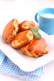 Cheese buns with cherry jam. Blue cup with milk. Stock Photography