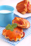 Cheese buns with cherry jam. Blue cup with milk. Royalty Free Stock Photography