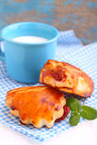 Cheese buns with cherry jam. Blue cup with milk Royalty Free Stock Image