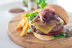 Cheese Burger. Big mouth cheese burger served with french fries on wooden cutting board Stock Photo