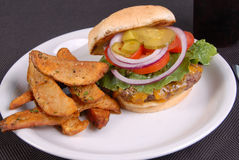 Cheese burger and fries with toppings. Cheese burger and fries loaded with onion, tomato, pickle, and lettuce served with potato wedges ready to eat Royalty Free Stock Photos