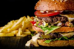 Cheese burger with grilled meat, cheese, tomato and potatoes on dark wooden surface. Ideal for advertisement. Close-up