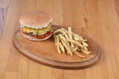 Cheese Burger. Served on a wooden plate with potato Royalty Free Stock Photo
