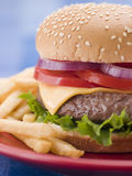 Cheese Burger in a Sesame Seed Bun with Fries Royalty Free Stock Photo