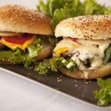 Cheese burgers. Two cheese burgers with swiss cheese and good steaks Stock Image