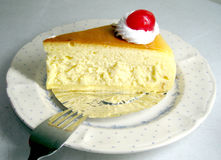 Cheese cake. A slide of lemon cheese cake with cherry on top Stock Photos