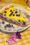 Cheese cake with blueberries. Cheese cake with blueberries piece lies on a plate next to flowers Royalty Free Stock Photos
