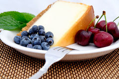 Cheese Cake, Cherries And Blueberries. Seasonal fruit with a slice of plain cheese cake with a mint leaf garnish served on a white saucer. Blueberries and Bing Stock Photos