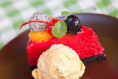 Cheese cake and ice-cream on plate  with fruit topping. Stock Photo