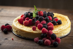 Cheese cake with rasberries on a wooded table Royalty Free Stock Images