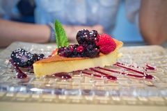 Cheese cake with red fruits and mint leaf in glass tray Stock Image
