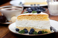 Cheese cake and tea with blue berry and mint on wooden table Stock Image