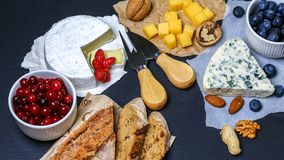 Cheese camembert, blue cheese, toasts, berries and walnut on a dark background. Flat top view. Copy space stock photo