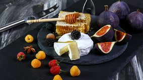 Cheese Camembert with figs, raspberry and blackberries on old black wooden table. Food for wine and romantic, cheese and bread. Delicatessen. Text area space stock image